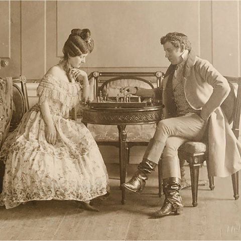 Foto: Adliges Paar Anfang des 20sten Jahrhunderts in feiner Kleidung und die Frau mit Hochsteckfrisur sitzt an einem kleinen Tisch und spielt Schach.
